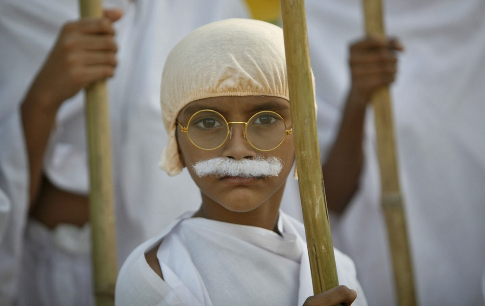 School boy dressed as Mahatma Gandhi takes part in march to mark the 143rd birth anniversary of Gandhi in Ahmedabad