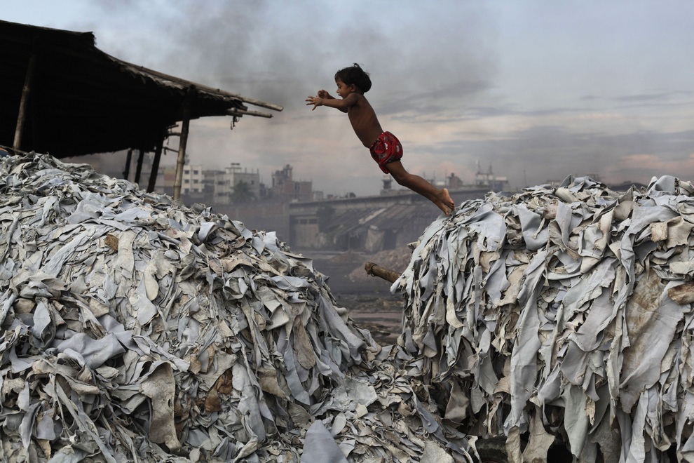 A child jumps on the waste products that are used to make poultry feed as she plays in a tannery at Hazaribagh in Dhaka