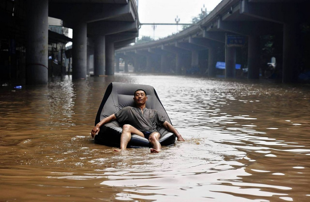 A man takes a nap on an inflatable sofa floating on a flooded street near the Yangtze River in Chongqing municipality