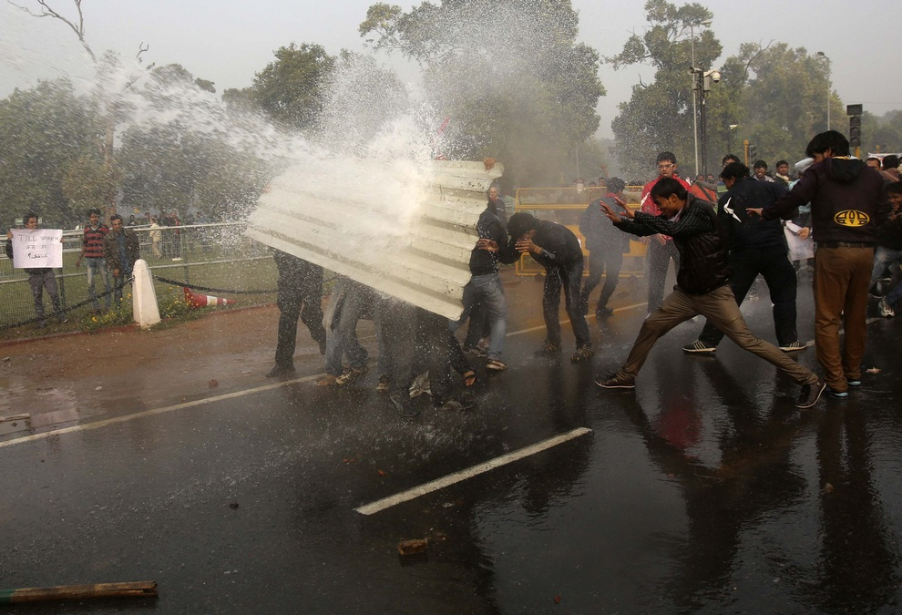 Demonstrators shield themselves from police water cannon in front of the India Gate during a protest in New Delhi