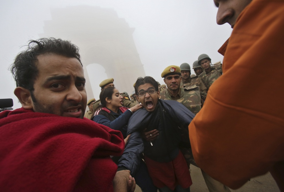 A demonstrator shouts slogans as he is detained by police in front of the India Gate during a protest in New Delhi