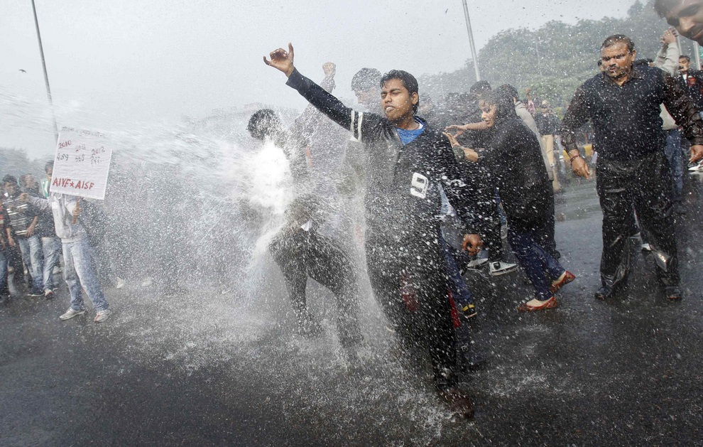 Demonstrators are hit by a police water cannon as they shout slogans during a protest in New Delhi
