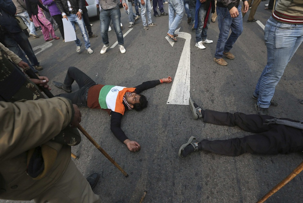 Demonstrators lie on the road in front of the India Gate during a protest in New Delhi