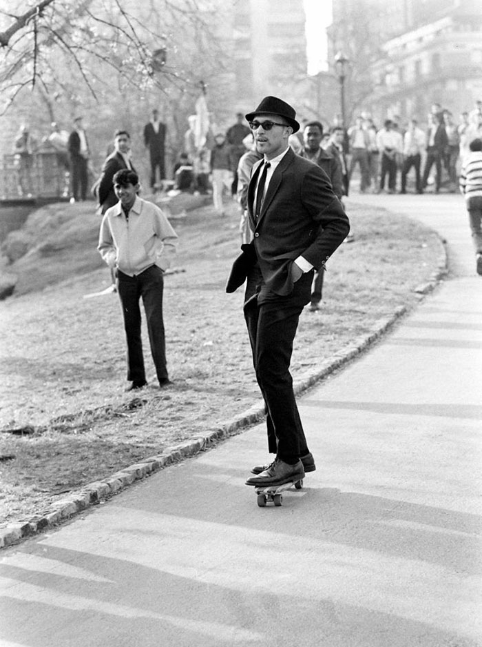 A Man In A Suit And Sunglasses Rides A Skateboard Down A Hill Path In Central Park, New York (1965)